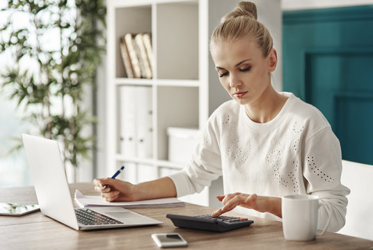 Concentrated woman budgeting at office