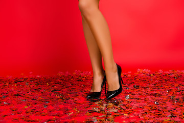 Cropped close up photo of sexual lovely skinny woman's legs and modern fashionable beautiful charming perfect high-heeled shoes standing against red background on floor covered with golden stars