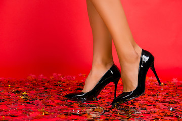 Close up cropped photo of stylish shiny elegant ideal perfect charming beautiful trendy black woman's shoes isolated on red background floor covered with confetti