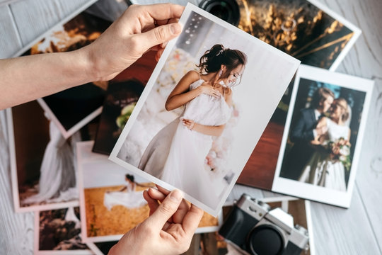 Printed wedding photos with the bride and groom, a vintage black camera and woman hands with photo