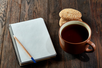 Cup of tea with cookies, workbook and a pencil on a wooden background, top view