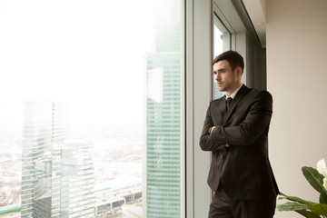 Pensive businessman standing near large window in office and looking on urban landscape with skyscrapers outside. Serious business leader pondering difficult decision, thinking about future challenges