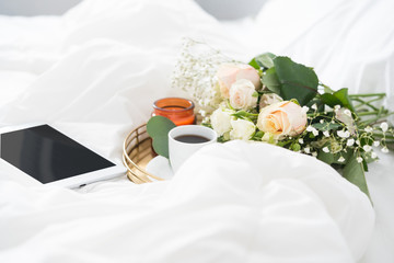 Happy morning in bed. Tablet and tray with bouquet, coffe and candle