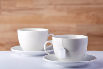 Two cups of tea and a teabag on white table on rustic wooden background, close-up, selective focus