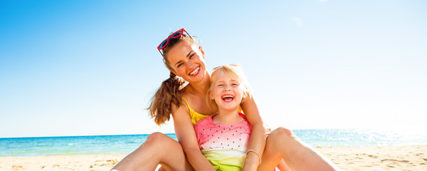 happy trendy mother and daughter sitting on beach