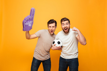 Portrait of a two joyful young men holding soccer ball
