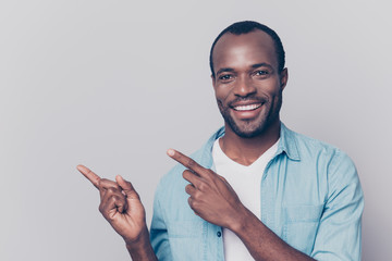 Portrait with empty place of sexy, virile, stunning man with beaming smile pointing two forefingers to copy space, looking at camera, isolated on grey background