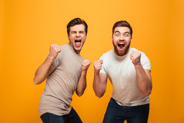 Portrait of a two cheerful young men celebrating
