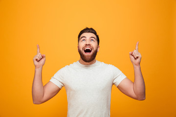 Portrait of a happy bearded man pointing fingers up Wall mural