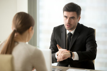 Angry company head pointing at watch scolding female employee for being late at work, hurrying manager to finish important job before deadline. Boss losing patience because of non-punctual worker