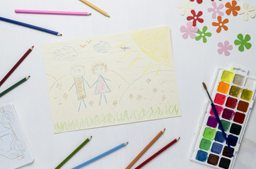 Simple drawing of a child, colored pencils and paint on a white background. The view from the top.