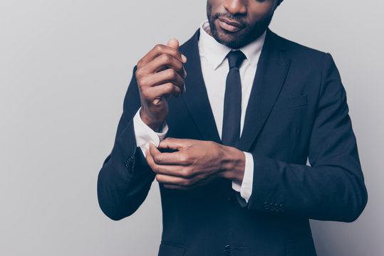 Cropped half face portrait of trendy, attractive, stunning man in black tuxedo with tie fasten button on sleeve cuffs of his white shirt, isolated on grey background