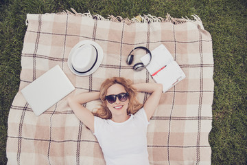 White casual t-shirt read copybook listen music bluetooth earphones spring open-air peace pleasure people person lifestyle leisure concept. Cute lovely lady enjoying fresh air lying checkered blanket
