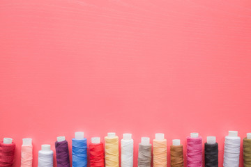 Colorful spools of threads on the pastel pink background. Mock up for dressmakers or textile shops offers as advertising or other ideas. Womanly hobby. Sewing concept. Empty place for text or a logo.