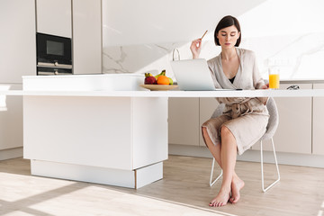 Smart brunette woman wearing bathrobe sitting at table in flat, and working on laptop while having breakfast