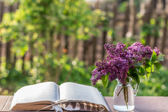 Bouquet of lilac flowers, book and owl feather with beautiful green nature background