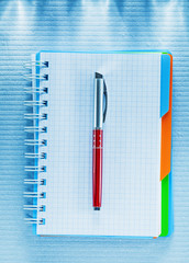 Blank checked notebook biro pen