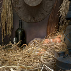 Still life visual art of chicken eggs in the nest in the old barn with dried rice straw, old lamp and old wine bottle