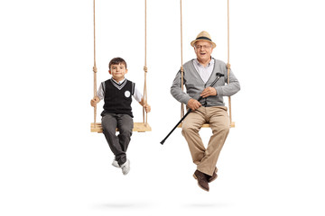 Little schoolboy and a mature man seated on swings