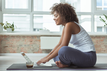 Side view cheerful african woman typing on digital device while locating on floor in room. She drinking cup of coffee