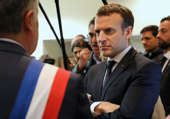 French President Emmanuel Macron listens to Les Mureaux Mayor François Garay during a visit at a mediatheque in Les Mureaux