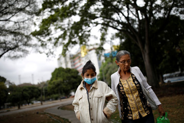 Yasmira Castano, 40, who lost her transplanted kidney, walks helped by her mother after she received a dialysis session at a state hospital in Caracas