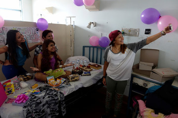 Lismar Castellanos, 21, who lost her transplanted kidney, poses for a selfie with her mother and friends during her birthday celebration at a state hospital in Caracas