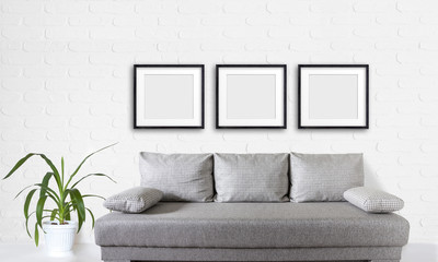 Three blank frames set over modern couch, and yucca plant in white flower pot near bricks wall, interior decor mock up.