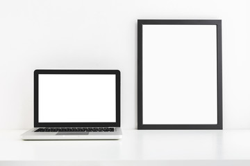 Laptop and a poster frame. Black and white color mock up.