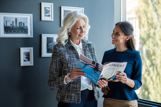 Article about our company. Elegant gorgeous old woman is standing with her young attractive female colleague near window while holding opened business journal and expressing interest