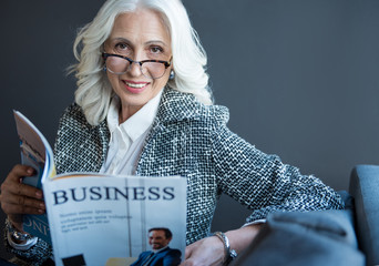 Business news. Portrait of optimistic charming gray-haired senior lady in glasses is sitting on sofa and holding journal while looking at camera with smile. She is reading article in magazine