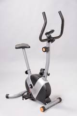 An exercise bicycle against a plain grey background