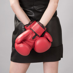Woman in a black dress and red boxing gloves