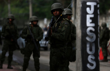 Members of armed forces patrol the Kelson's slum during an operation against crime in Rio de Janeiro