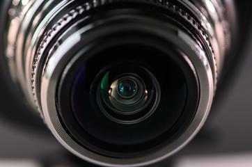 .The camera lens and light gray. Horizontal photo.