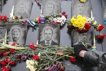 A participant lays flowers during a commemoration ceremony at the monument to the people killed during the 2014 Ukrainian pro-European Union protests in Kiev