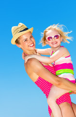 smiling modern mother and child on seashore
