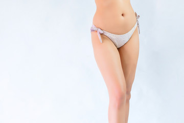 Part body of sexy asia woman in the white bikini. Slim and shapely body is posing on isolate white background.