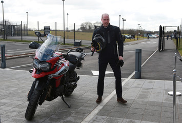 Britain's Prince William stands next to a motorbike after riding it during a visit to Triumph Motorcycles in Hinckley