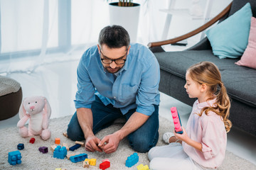 little daughter and father playing with colorful blocks together on floor at home