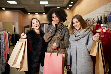Women of diverse ethnicity with shopping bags posing in mall. Portrait of three pretty multiracial girls walking at lingerie and clothing store on sale. Copyspace on large paper craft bags.