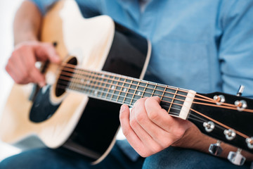 cropped shot of man playing acoustic guitar at home