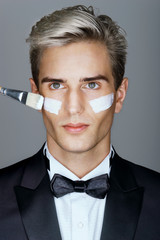 Classy gentleman with a facial cream. Photo of handsome man applying moisturizer cream to his face. Beauty & Skin care concept.