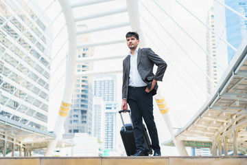 Business man walking at outdoors with luggage in the routine of working with determination and confidence. concept of business trip travel and transportation.