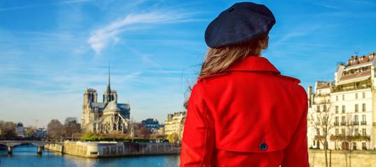 woman on embankment near Notre Dame de Paris in Paris, France