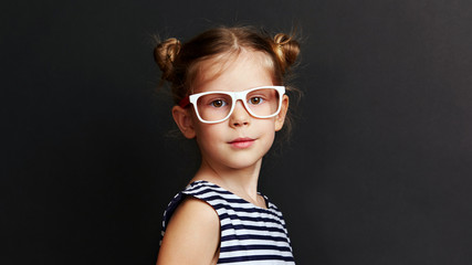Beautiful girl in stylish optical glasses over dark background. Vision concept.