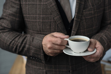 cropped shot of man in tweed suit with cup of coffee