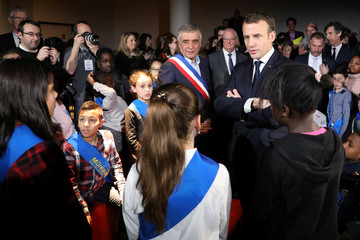 """French President Emmanuel Macron and Les Mureaux Mayor François Garay talk with children of the town council at the digital museum """"Micro-Folie"""" during a visit at a mediatheque in Les Mureaux"""