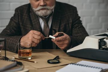 cropped shot of senior writer burning match for smoking pipe