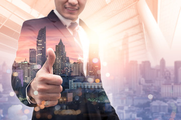 The double exposure image of the businessman make a thumbs up during sunrise overlay with cityscape image. The concept of liking, interest, popularity, modern life, business, city life and partnership